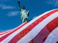 NEW YORK, NY - JULY 20: The Statue of Liberty is seen over a wind blown American flag scarf on Liberty Island on July 20, 2020 in New York City. Liberty Island partially reopens months after the attraction was shut down due to the coronavirus pandemic. Access to Liberty Island …