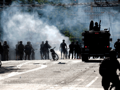 """Police and protesters clash at the intersection of Broadway and East Pine Street following the """"Youth Day of Action and Solidarity with Portland"""" demonstration in Seattle, Washington on July 25, 2020. - Police in Seattle used flashbang grenades and pepper spray Saturday against protesters who set fire to construction trailers …"""