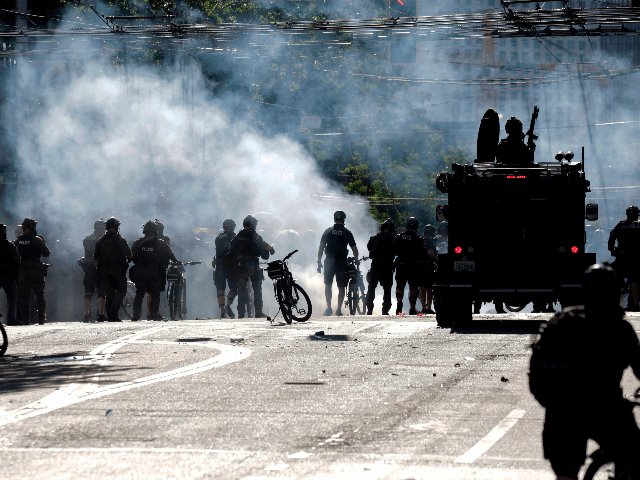 "Police and protesters clash at the intersection of Broadway and East Pine Street following the ""Youth Day of Action and Solidarity with Portland"" demonstration in Seattle, Washington on July 25, 2020. - Police in Seattle used flashbang grenades and pepper spray Saturday against protesters who set fire to construction trailers …"