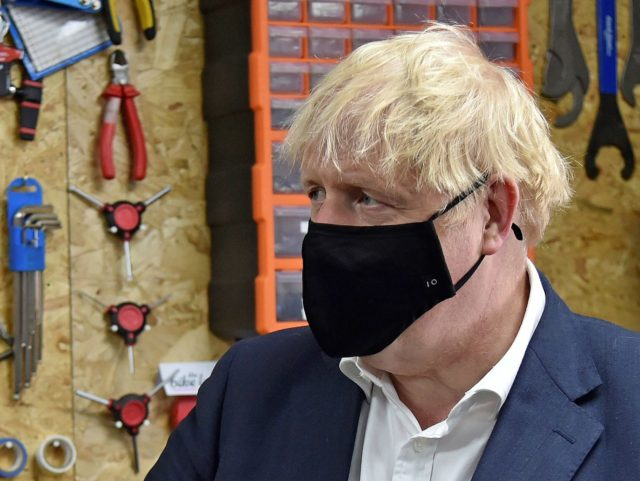 Britain's Prime Minister Boris Johnson wearing a black face mask featuring a number '10', due to the COVID-19 pandemic, talks to the owner of the the Cycle Lounge, Rodney Rouse, a bicycle repair shop in Beeston, central England, on July 28, 2020, during an event to launch the the government's …