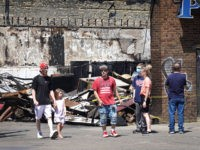 MINNEAPOLIS, MINNESOTA - JUNE 03: People walk past the charred remains of a pawn shop destroyed during last week's rioting on June 3, 2020 in Minneapolis, Minnesota. Protests marred by rioting and looting in some places erupted after Floyd died May 25 while in the custody of Minneapolis police. (Photo …