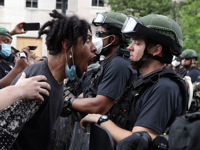 WASHINGTON, DC - JUNE 03: A demonstrator shouts a law enforcement officer during a peaceful protest against police brutality and the death of George Floyd, on June 3, 2020 in Washington, DC. Protests in cities throughout the country have been been held after the death of George Floyd, a black …