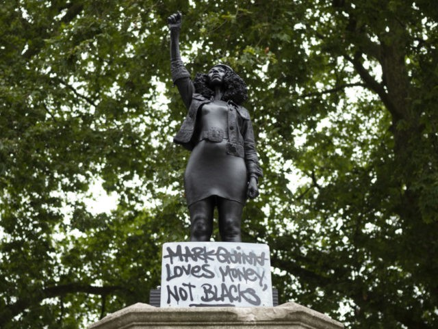 "BRISTOL, ENGLAND - JULY 15: A sign saying ""Marc Quinn loves money not blacks"" is placed on a new sculpture, by local artist Marc Quinn, of Black Lives Matter protestor Jen Reid on the plinth where the Edward Colston statue used to stand on July 15, 2020 in Bristol, England. …"