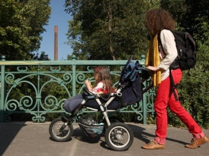 BERLIN, GERMANY - SEPTEMBER 16: A mother pushes her three-year-old daughter in a stroller on September 16, 2012 in Berlin, Germany. Germany is currently debating the introduction of a nation-wide home child care subsidy (Betreuungsgeld), which would provide parents of one to three-year-old children the option of receiving EUR 150 …