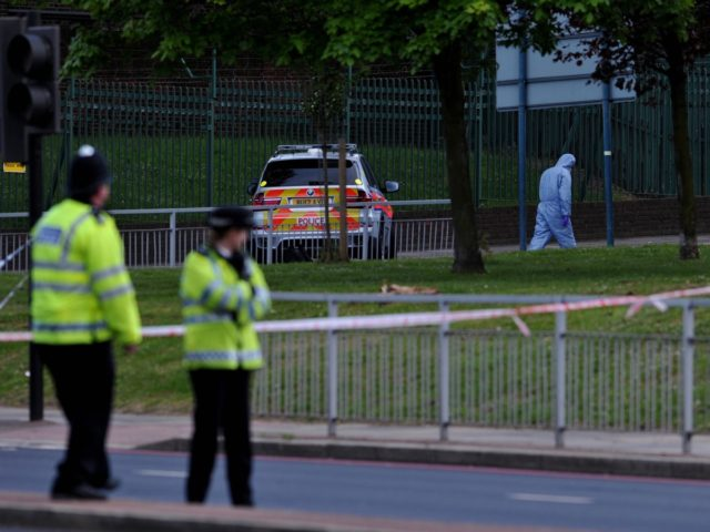 Police forensics officers search a cordoned off area in Woolwich, east London, on May 22, 2013, following an incident in which one man was killed and two others seruiously injured. British police shot and wounded two men after a man thought to be a serving soldier was killed outside a …