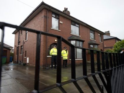 Police officers stand guard outside the family home of one of nine British citizens currently detained by Turkish authorities for allegedly attempting to illegally enter Syria from Turkey, in Rochdale, northern England on April 3, 2015. The property is thought to be the home of British local councillor councillor Shakil …