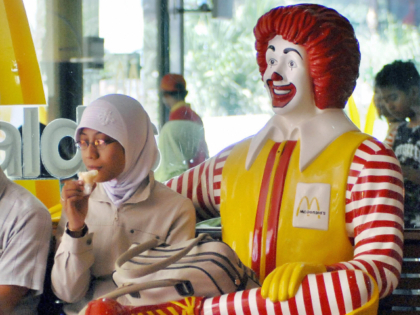 Yogyakarta, INDONESIA: A Muslim woman eats ice cream next to a statue of Ronald McDonald in Yogyakarta 12 January 2007. Most of Indonesia's Muslims, who make up around 90 percent of the population of 220 million, practise a moderate and tolerant form of the religion. AFP PHOTO/Bay ISMOYO (Photo credit …