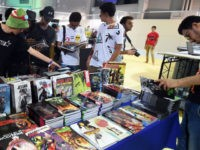 Young Tunisians look through copies of comic books and graphic novels during the opening of the second edition of Comic Con Tunisia on July 7, 2017, in the town of Le Kram, north of Tunis. / AFP PHOTO / FETHI BELAID (Photo credit should read FETHI BELAID/AFP via Getty Images)