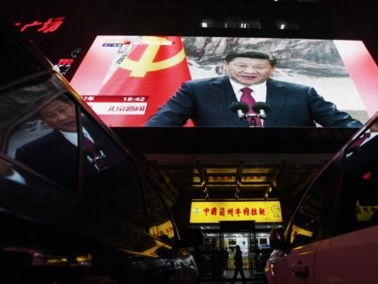 TOPSHOT - People walk outside a shop below a screen showing news coverage about Chinese President Xi Jinping, in Beijing on October 25, 2017. Chinese President Xi Jinping was formally handed a second term on October 25, 2017, with no clear successor emerging in a revamped ruling council, cementing his …