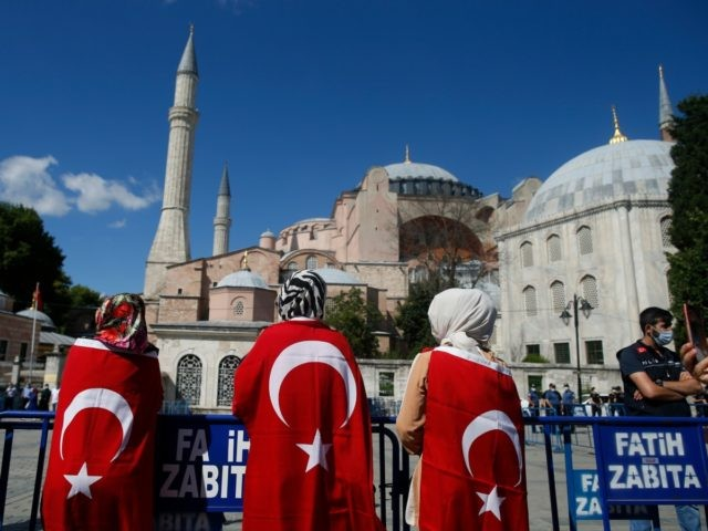 People, draped in Turkish flags, gather outside the Byzantine-era Hagia Sophia, one of Istanbul's main tourist attractions in the historic Sultanahmet district of Istanbul, following Turkey's Council of State's decision, Friday, July 10, 2020.Turkey's Council of State, threw its weight behind a petition brought by a religious group and annulled …