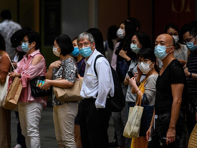 Pedestrians wear face masks as they wait to cross a road in Hong Kong on July 10, 2020, as the city experiences new local outbreaks of the COVID-19 coronavirus. - The finance hub recorded 38 new confirmed cases on July 10, thirty-two of which were locally transmitted. (Photo by Anthony …