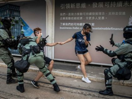 TOPSHOT - Police chase down a couple wearing facemasks in the central district in Hong Kong on October 5, 2019, a day after the city's leader outlawed face coverings at protests invoking colonial-era emergency powers not used for half a century. - Masked pro-democracy protesters marched through Hong Kong in …
