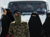 TOPSHOT - An internal security patrol member escorts women, reportedly wives of Islamic State (IS) group fighters, in the al-Hol camp in al-Hasakeh governorate in northeastern Syria, on July 23, 2019. - Stabbing guards, stoning aid workers and flying the Islamic State group's black flag in plain sight: the wives …