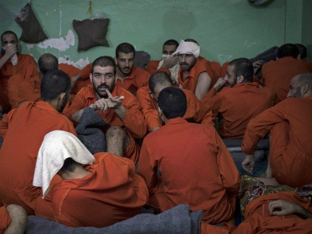 Men, suspected of being affiliated with the Islamic State (IS) group, gather in a prison cell in the northeastern Syrian city of Hasakeh on October 26, 2019. - Kurdish sources say around 12,000 IS fighters including Syrians, Iraqis as well as foreigners from 54 countries are being held in Kurdish-run …