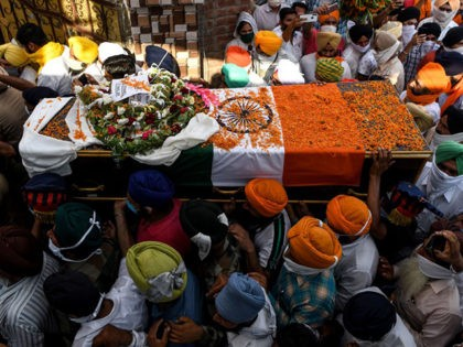 Family members and villagers carry the coffin of soldier Satnam Singh who was was killed in a recent clash with Chinese forces in the Galwan valley area, during the cremation ceremony at Bhojraj village near Gurdaspur on June 18, 2020. - India and China agreed on June 17 to ease …