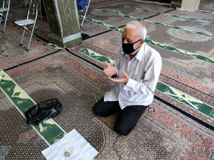 A mask-clad Iranian man prays at a mosque in the capital Tehran, amid the ongoing novel coronavirus pandemic crisis, on July 19, 2020. - Iran's president said yesterday that 35 million Iranians may contract the coronavirus, as the country still did not have herd immunity although a quarter of the …
