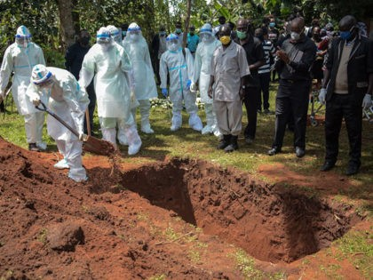 Members of Bungoma County Isolation Team in personal protection equipment (PPE) bury the coffin of Dr. Doreen Lugaliki, 39, the first Kenyan doctor who died of the COVID-19 coronavirus in Nairobi, during her funeral in Ndalu, western Kenya, on July 13, 2020. (Photo by Brian ONGORO / AFP) (Photo by …