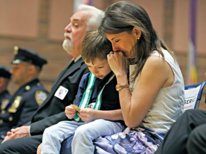 Lisa Tuozzolo, widow of deceased New York Police Department Sgt. Paul Tuozzolo, weeps as her son Austin looks at the NYPD's Medal of Honor he accepted posthumously for his father during the New York Police Department's Medal Day honoring police officers and their families who put their lives on the …