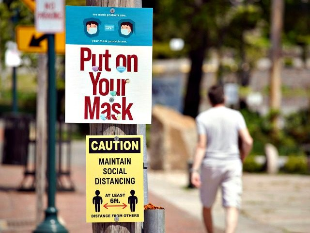 A man walks along a sidewalk on Main Street where signs encourage people to wear masks and maintain social distancing in Ogunquit, Maine, on May 27, 2020. Gregory Rec/Portland Press Herald via Getty Images Maine residents are required to w