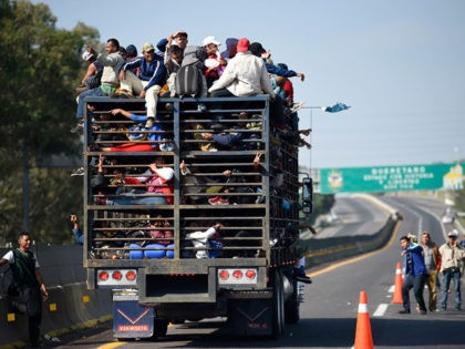 Central American migrants -mostly honduran- taking part in a caravan to the US, are pictured on board a truck heading to Irapuato in the state of Guanajuato on November 11, 2018 after spending the night in Queretaro in central Mexico. - The United States embarked Friday on a policy of …