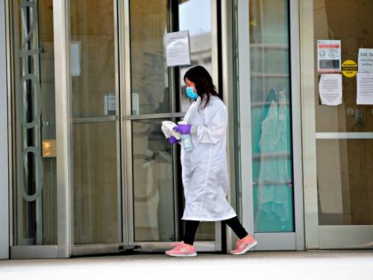 women cleans the entrance doors to Moderna headquarters in Cambridge, Massachusetts on May 18, 2020. - US biotech firm Moderna reported promising early results from the first clinical tests of an experimental vaccine against the novel coronavirus performed on a small number of volunteers. The Cambridge, Massachusetts-based company said the …