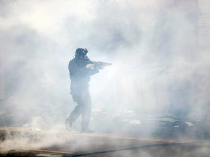 A police officer moves through tear gas deployed to disperse a crowd as Justice for George Floyd Philadelphia Protests continue Sunday, May 31, 2020, in Philadelphia. Protests were held throughout the country over the death of Floyd, a black man who died after being restrained by Minneapolis police officers on …