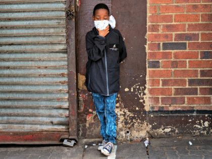 A young boy wearing a makeshift mask waits in line to access a grocery store in the Hillbrow district of downtown Johannesburg, South Africa, Friday, April 10, 2020. South African President Cyril Ramaphosa extended the lockdown by an extra two weeks in a continuing effort to contain the spread of …