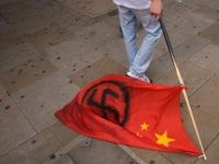 A man drags a Chinese flag daubed with a Nazi swastika along the ground during a protest by UK Uighurs and their supporters in central London, on July 15, 2009. The demonstration was protesting against the Chinese crackdown on protests by the Uighur people of the Xinjiang district, known as …