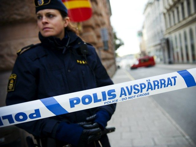 A police officer stands guard as a police and fire department team inspects a street and building where a suspicious package was found, next to the Rosenbad government office, in Stockholm, on October 13, 2011. Police said they had evacuated parts of Sweden's government building, which houses Prime Minister Fredrik …