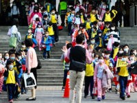 Children wearing face masks leave their elementary school at the end of the day in Xindian district, New Taipei City on March 3, 2020. - The world has entered uncharted territory in its battle against the deadly coronavirus, the UN health agency warned, as new infections dropped dramatically in China …