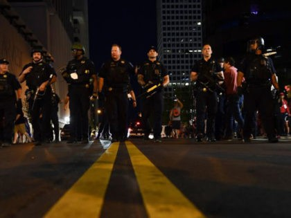 Police officers march towards the crowd where Trump supporters and anti-Trump protestors now roam the same area in Tulsa, Oklahoma where Donald Trump held a campaign rally earlier on June 20, 2020. - Hundreds of supporters lined up early for Donald Trump's first political rally in months, saying the risk …