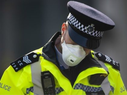 LONDON, ENGLAND - APRIL 09: A police officer in a mask stands guard outside St Thomas' Hospital on April 09, 2020 in London, England. Prime Minister Boris Johnson is still being cared for in the intensive care unit at St Thomas' Hospital after his coronavirus symptoms worsened on Monday night. …