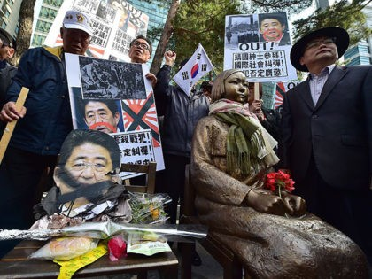 "South Korean protestors place a damaged portrait (L) of Japan's Prime Minister Shinzo Abe next to a statue (R) of a South Korean teenage girl in traditional costume called the ""peace monument"" for former ""comfort women"" during an anti-Japan rally outside the Japanese embassy in Seoul on April 1, 2015. …"