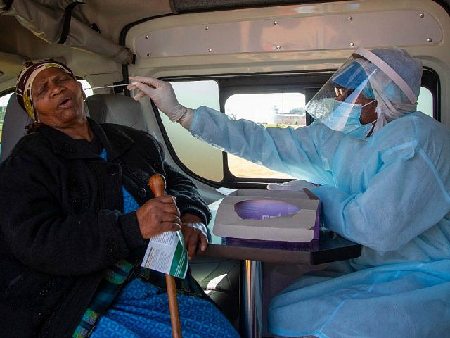 An elderly woman reacts as a heath worker collects a sample for coronavirus testing during the screening and testing campaign aimed to combat the spread of COVID-19 at Sphamandla informal settlement in Katlehong, south of Johannesburg, South Africa, Friday, May 22, 2020. (AP Photo/Themba Hadebe)