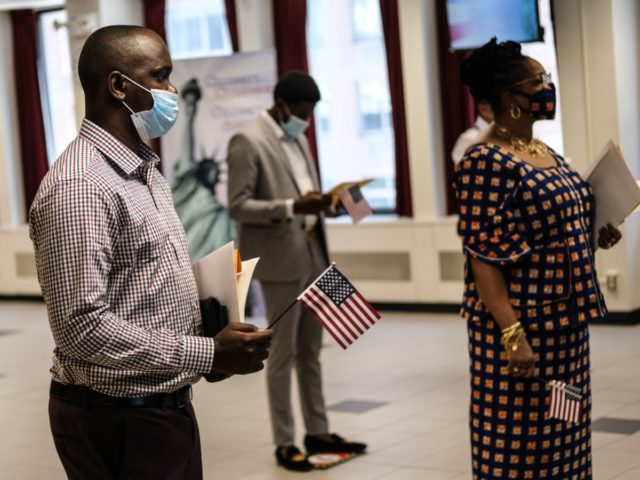NEW YORK, NY - JULY 02: People are sworn in as new American citizens during a ceremony at the U.S. Citizenship and Immigration Services New York Field Office on July 2, 2020 in New York City. The ceremonies were brief and observed precautions, like wearing a mask and adhering to …