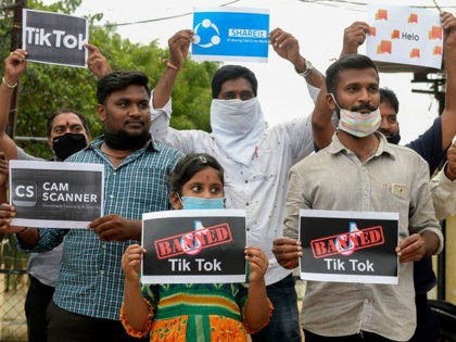 Members of the City Youth Organisation hold posters with the logos of Chinese apps in support of the Indian government for banning the wildly popular video-sharing 'Tik Tok' app, in Hyderabad on June 30, 2020. - TikTok on June 30 denied sharing information on Indian users with the Chinese government, …