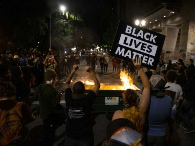 CORRECTS DAY AND DATE TO FRIDAY JULY 10. - In this Friday, July 10, 2020 file photo, a waste receptacle's contents are in flames as protesters gather in downtown Portland, Ore. The mayor of Portland, Oregon said late Sunday the U.S. Marshals Service are investigating the injury of a protester …