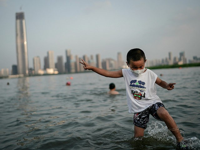 WUHAN, CHINA - JUNE 30: (CHINA OUT) A boy wearing a face mask plays in a flooded Jiangtan park caused by heavy rains along the Yangtze river on June 30, 2020 in Wuhan, China. Since June 13, 2020 the response level of public health emergencies in Hubei Province has been …