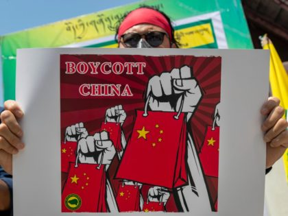 An exile Tibetan activist holds a banner during a street demonstration by the Tibetan Youth Congress asking for a boycott of Chinese goods in Dharmsala, India, Tuesday, June 16, 2020. (AP Photo/Ashwini Bhatia)