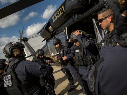 Members of the U.S. Customs and Border Protection, Office of Field Operations Special Response Team, gather outside an AMO UH-60 Black Hawk helicopter after an air-intercept training exercise as they provide airspace security for Super Bowl LI, in Conroe, Texas, Feb. 1, 2017. Units with Air and Marine Operations and …