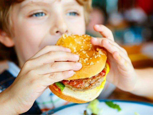 Cute healthy preschool kid boy eats hamburger sitting in cafe outdoors.