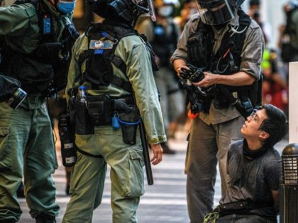 A protester (centre R) is detained by police during a rally against a new national security law in Hong Kong on July 1, 2020, on the 23rd anniversary of the city's handover from Britain to China. - Hong Kong police arrested more than 300 people on July 1 -- including …