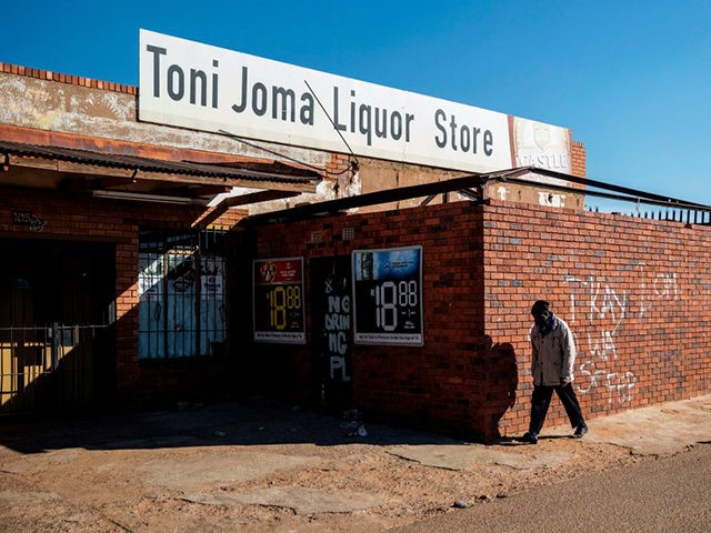 A man walks past a closed liquor shop in Soweto, on July 13, 2020. - South African President Cyril Ramaphosa on July 12, 2020 re-imposed a night curfew and suspended alcohol sales as COVID-19 coronavirus infections spiked and the health system risked being overwhelmed. (Photo by Michele Spatari / AFP) …