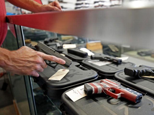 A worker restocks handguns at Davidson Defense in Orem, Utah on March 20, 2020. - Gun stores in the US are reporting a surge in sales of firearms as coronavirus fears trigger personal safety concerns. (Photo by GEORGE FREY / AFP) (Photo by GEORGE FREY/AFP via Getty Images)