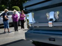 FREEHOLD, NEW JERSEY - JUNE 09: People view the coffin of Lieselotte Tonon, 85, outside the Clayton and McGirr Funeral Home during a drive-by viewing on June 09, 2020 in Freehold, New Jersey. The funeral home began offering outdoor drive-by services to families to help larger numbers of people pay …