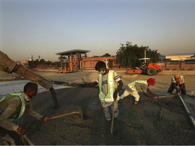 Road construction workers build a toll plaza on a highway in Ghaziabad, on the outskirts of New Delhi, India, May 16, 2020. India's lockdown, imposed March 25, is set to at least partially end May 18. Some restrictions on manufacturing, agriculture and self-employment were lifted May 4 to ease the …