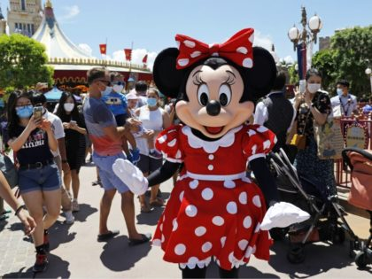The iconic cartoon character Minnie Mouse waves to visitors at the Hong Kong Disneyland on Thursday, June 18, 2020. Hong Kong Disneyland on Thursday opened its doors to visitors for the first time in nearly five months, at a reduced capacity and with social distancing measures in place. The theme …