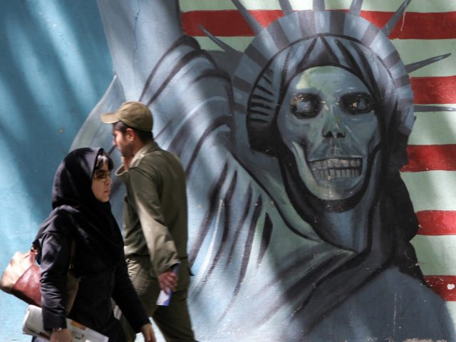 Tehran, IRAN: Iraniana walk past an anti-US mural painting depicting the Statue of Liberty on the wall of the former US embassy in Tehran, 08 May 2006. Iranian President Mahmoud Ahmadinejad has written a letter to US President George W. Bush, which is to be handed to the Swiss embassy, …