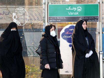 People wearing protective masks stand at a bus station in the Iranian capital Tehran on March 2, 2020, following the COVID-19 illness outbreak, which Iran says has claimed 66 lives out of 1,501 cases of infection since February. - The novel coronavirus has sparked intense debate in Iran between ultra-conservative …