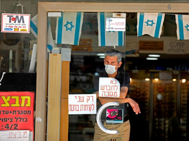 A man wearing a protective mask amid the Covid-19 pandemic stands in a shop with a sign on the window reading in Hebrew: please wear a mask in the centre of Jerusalem on July 7, 2020. - As of today, Israel had recorded more than 31,000 coronavirus cases, including 338 …